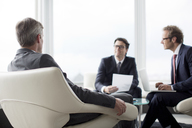 Businessmen talking in office lobby - CAIF01657