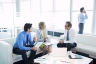 Business people talking in office lobby - CAIF01663