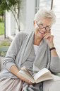 Woman reading book on porch swing - CAIF01672