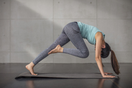 Young woman doing yoga exercise in studio - ZEF15099