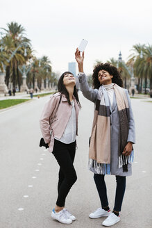 Spain, Barcelona, two happy women taking a selfie on promenade - EBSF02149