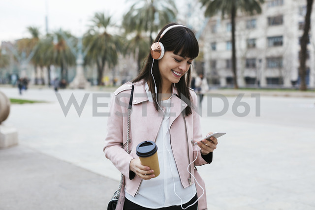 Spain, Barcelona, smiling woman with coffee, cell phone and headphones in the city - EBSF02152 - Bonninstudio/Westend61