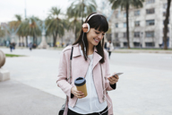 Spain, Barcelona, smiling woman with coffee, cell phone and headphones in the city - EBSF02152