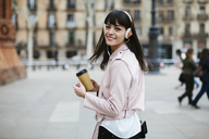 Spain, Barcelona, smiling woman with coffee and headphones in the city - EBSF02158
