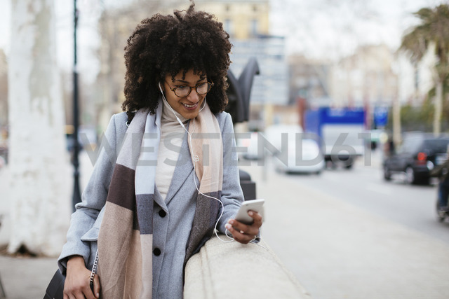 Spain, Barcelona, smiling woman with cell phone and earphones in the city - EBSF02167 - Bonninstudio/Westend61