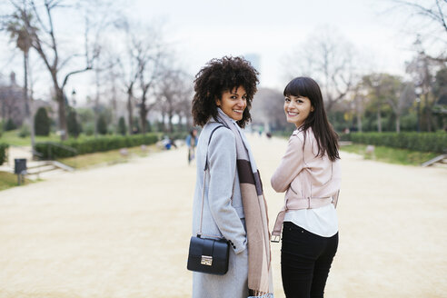 Spain, Barcelona, portrait of two smiling women in city park turning round - EBSF02176