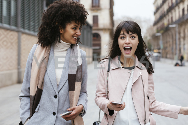 Spain, Barcelona, two female friends with cell phones in the city - EBSF02188 - Bonninstudio/Westend61