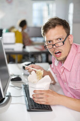 Businessman eating Chinese food at desk - CAIF01843