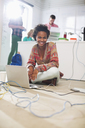 Businesswoman using laptop on floor - CAIF01846