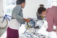 Business people untangling cords in office - CAIF01849
