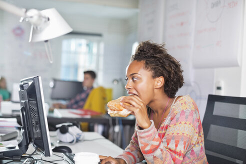 Businesswoman eating burger at desk - CAIF01852