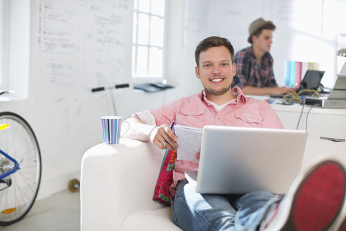Businessman using laptop on sofa in office - CAIF01855