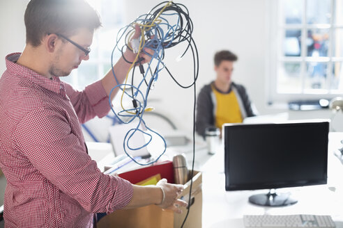 Businessman untangling cords in office - CAIF01858