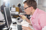 Businessman eating Chinese food at desk - CAIF01864