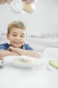 Smiling boy having spaghetti at table - CAIF01915
