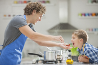 Father and son cooking in kitchen - CAIF01930