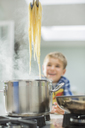 Boy watching parent cook spaghetti - CAIF01936