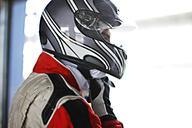 Racer tying on helmet in garage - CAIF01984