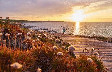 Italy, Sardinia, Lu Litarroni, senior woman on wooden boardwalk at sunset - MRF01891