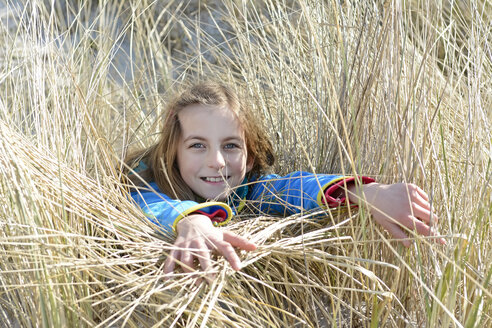 Germany, Hiddensee, portrait of smiling girl lying in grass of dunes - BFRF01821