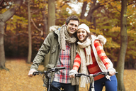 Couple riding bicycles together in park - CAIF02057
