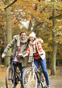 Couple riding bicycles together in park - CAIF02060