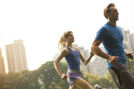 Couple running in urban park - CAIF02096