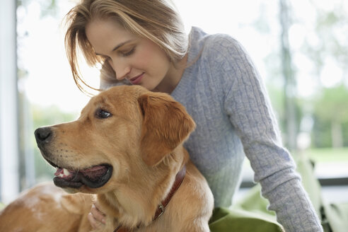 Woman relaxing with dog indoors - CAIF02210