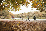 Family riding bicycles in park - CAIF02273