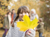 Girl holding autumn leaf in park - CAIF02294
