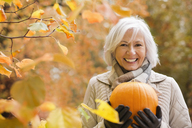 Older woman holding pumpkin in park - CAIF02309