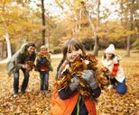 Family playing in autumn leaves - CAIF02312