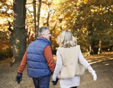 Older couple walking together in park - CAIF02321