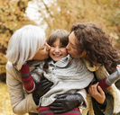 Woman and daughter kissing girl in park - CAIF02333