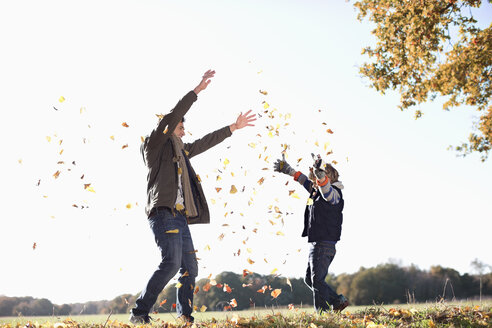 Father and son playing in autumn leaves - CAIF02336