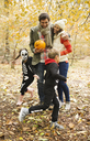 Couple with children in skeleton costumes in park - CAIF02348
