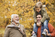 Three generations of men smiling in park - CAIF02369