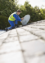 Worker installing satellite dish on roof - CAIF02411
