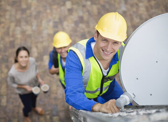 Workers installing satellite dish on roof - CAIF02432
