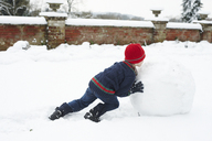 Boy making snowman outdoors - CAIF02435