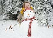 Girl making snowman outdoors - CAIF02444