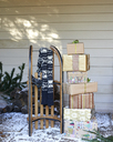Scarf, wooden sled and Christmas gifts on snowy porch - CAIF02447