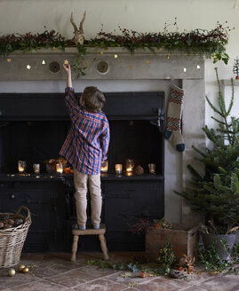 Boy decorating Christmas fireplace - CAIF02453