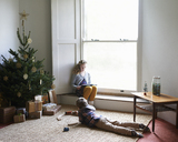 Children relaxing by Christmas tree - CAIF02459