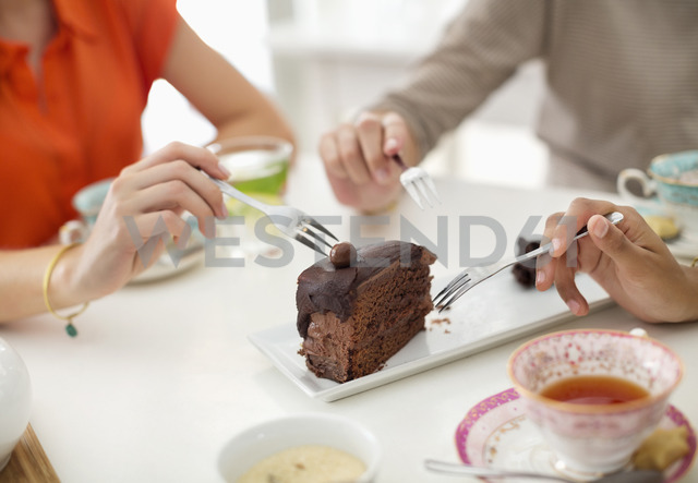 Women sharing slice of cake - CAIF02462