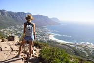 South Africa, Cape Town, woman standing looking at the coast during hiking trip to Lion's Head - ECPF00221