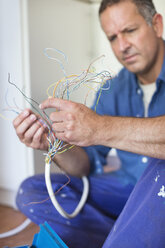 Electrician examining wires in kitchen - CAIF02548