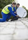 Workers installing satellite dish on roof - CAIF02560