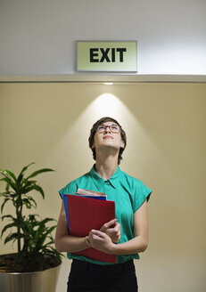 Businesswoman standing under office 'exit' sign - CAIF02590