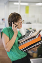 Businesswoman with folders talking on cell phone - CAIF02602